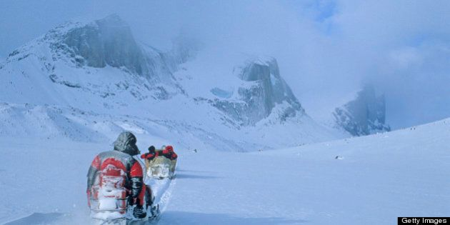 Inuit snowmobiles pull expedition members across a frozen