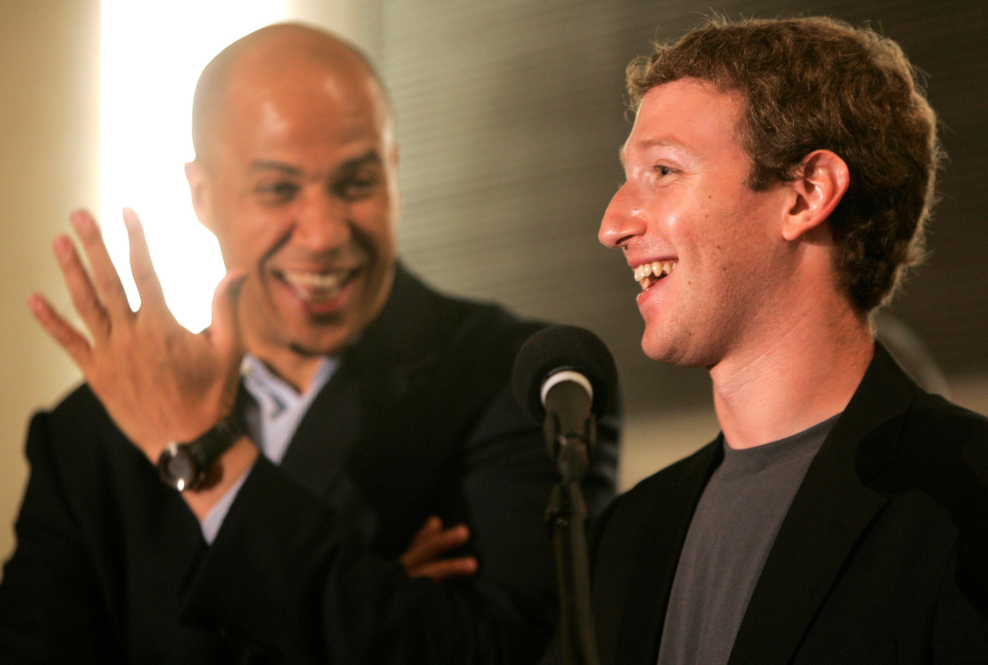 Newark Mayor Cory Booker, left, laughs as Mark Zuckerberg, right, founder and CEO of Facebook, talks about his donation of $100 million to help Newark public schools during a press conference at the Robert Treat Hotel in Newark, N.J., Saturday, Sept. 25, 2010. Also there is N.J. Gov. Chris Christie, not in picture. (AP Photo/Rich Schultz)