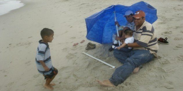 With Tropical Storm Gabrielle looming offshore, Jose and Minerva Perez tried to squeeze in a few extra minutes at the beach with their children Manuel, 3, left, and Raul, 6 months, Sunday, September 9, 2007 in Atlantic Beach, North Carolina. The weak tropical storm landed at the Outer Banks with 50mph winds.  (Photo by Jason Arthurs/Raleigh News & Observer/MCT via Getty Images)