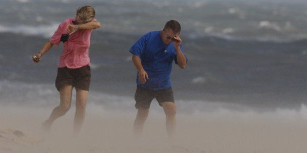 Karen and Mark Primeau, of Unionville, Virginia, brave wind-blown sand from Tropical Storm Gabrielle...