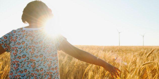 USA, Oregon, Wasco, Girl (10-11) walking in glorious sunshine amidst wheat