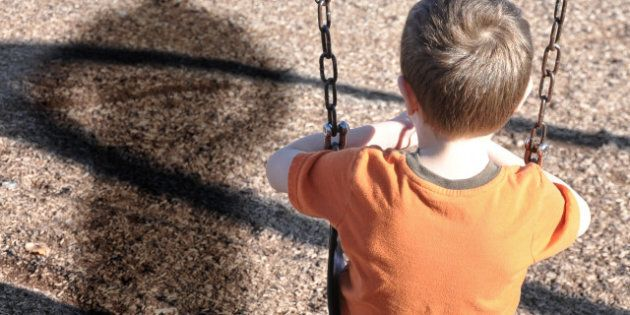 A young boy is sitting on a swing set and looking at a shadow figure of a man or bully at a playground....