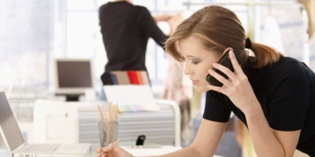 Young attractive female fashion designer leaning on office desk, talking on mobile