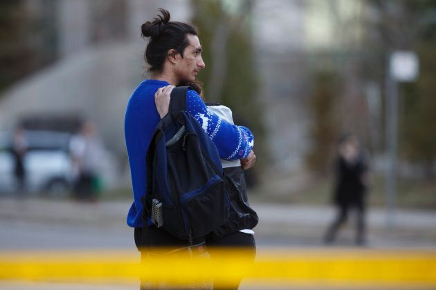 People embrace at the scene on Yonge St. at Finch Ave., after a van plowed into pedestrians on April...