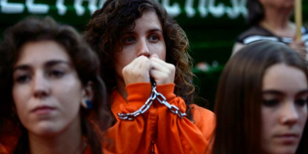 A Greenpeace activist in handcuffs takes part in a demonstration in support of 30 activists arrested...