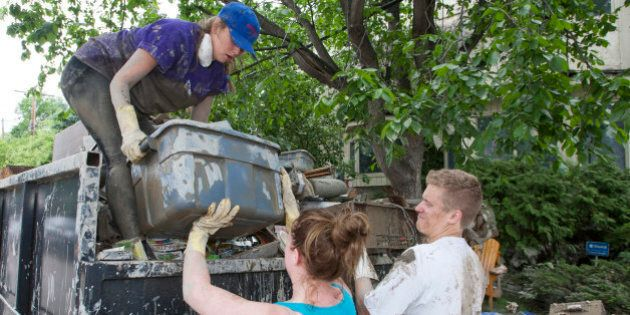 Emily Ebbels, left, Kyli Lane, center, and Charlie Hogarth help a friend's family clean up in Rideau...