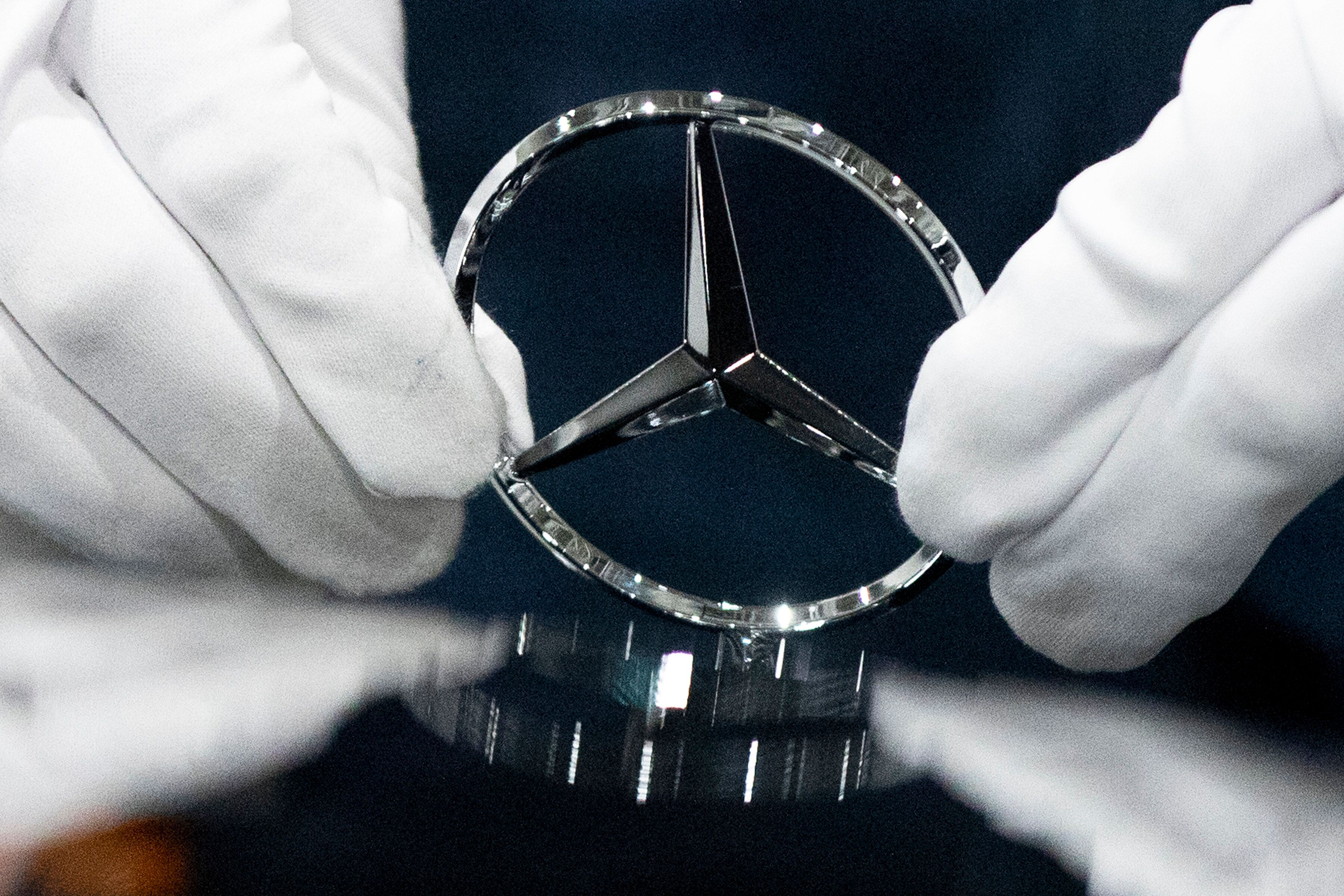 A worker wipes a logo of a car at the Mercedes Benz automobile assembly plant outside Moscow, Russia, Wednesday, April 3, 2019. Germany's Daimler AG has opened a new Mercedes factory in Russia, part of a 250 million euro ($281 million) investment it says will create 1,000 jobs. (AP Photo/Pavel Golovkin, Pool)