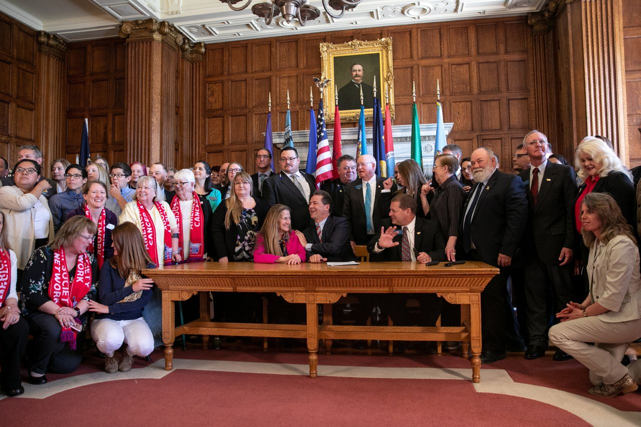 Democratic state Rep. Mary Caferro, left, and Republican state Rep. Ed Buttrey, right, just after Bullock (center) signed a bill to continue Montana's Medicaid expansion program on Thursday in Helena.