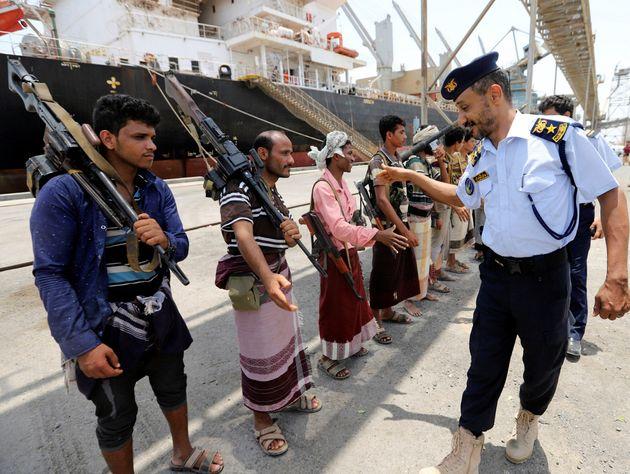 예멘 해안경비대 직원이 철수중인 후티 반군 대원들과 악수를 나누고 있다. 2019년