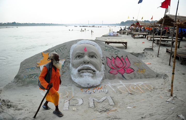 An sadhu walks past a sand sculpture of Prime Minister-designate Narendra Modi at the Sangam in Allahabad on May 26, 2014.