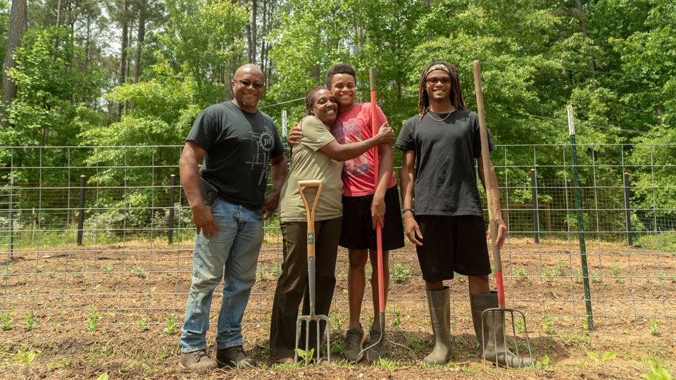 (L-R) Warren Cameron (husband), Keisha, and children Zachary and Abraham. The family owns High Hog Farm...