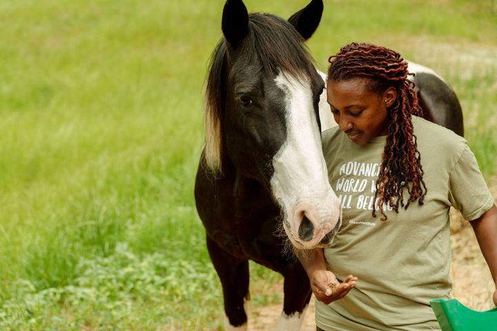 Keisha feeds her horse, Hercules, who helped inspire her to create the farm.
