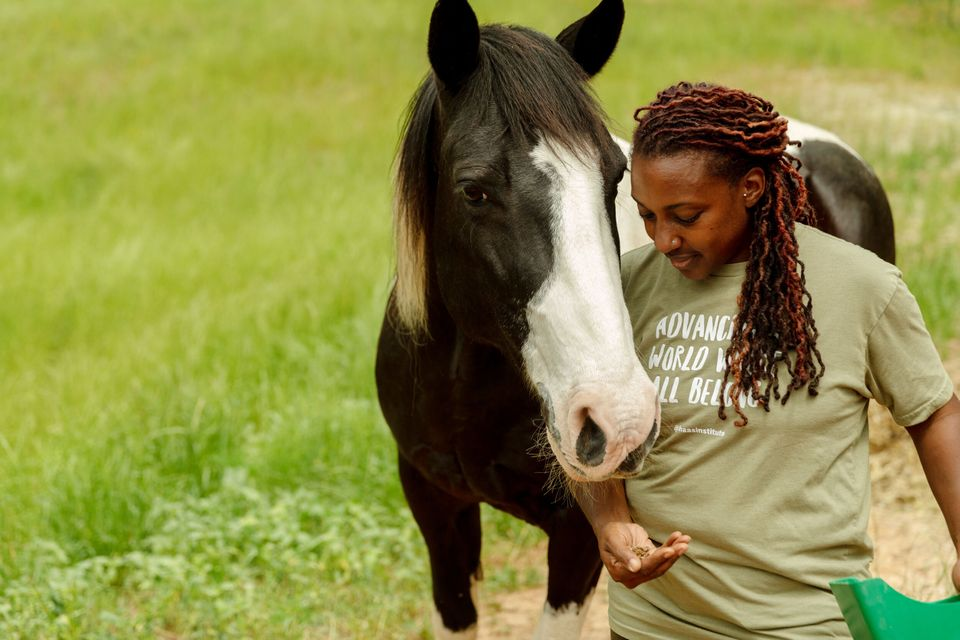 Keisha feeds her horse, Hercules, who helped inspire her to create the