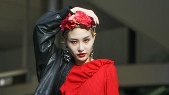 TOKYO, JAPAN - MARCH 21: A guest is seen wearing black leather jacket, red dress and flower head piece during the Amazon Fashion Week TOKYO 2019 A/W on March 21, 2019 in Tokyo, Japan. (Photo by Onnie A Koski/Getty Images)