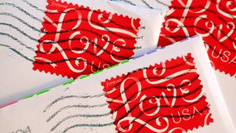 Colorful close up of three red love postage stamps attached to white envelopes