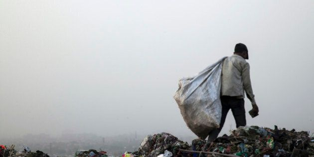 A rag picker carries a sack of sorted recyclable materials collected from garbage at the Ghazipur landfill...