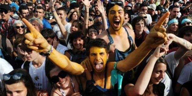 Festival-goers react during a concert of the band Detroit on July 19, 2014, during the 23rd edition of the Festival des Vieilles Charrues in Carhaix-Plouguer, western France. AFP PHOTO / FRED TANNEAU (Photo credit should read FRED TANNEAU/AFP/Getty Images)