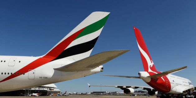 Airbus SAS A380-800 aircraft operated by Emirates Airline, left, and Qantas Airways Ltd. stand on the...