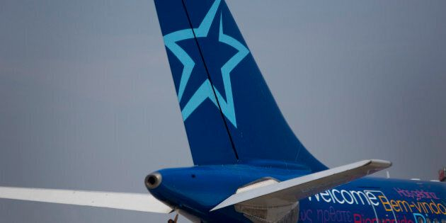 A worker inspects the rear of an Air Transat aircraft at Toronto Pearson International Airport in Toronto,...