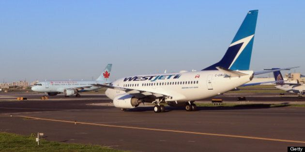 TORONTO, ON - AUGUST 28: A WestJet flight and an Air Canada flight cross paths on a runway at the Lester...