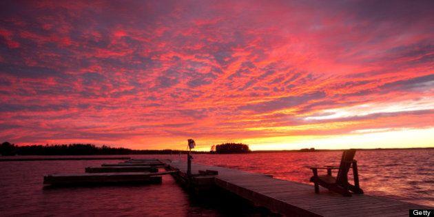 A beautiful sunset in the Muskoka region of Ontario. Dock with muskoka chair. Summer