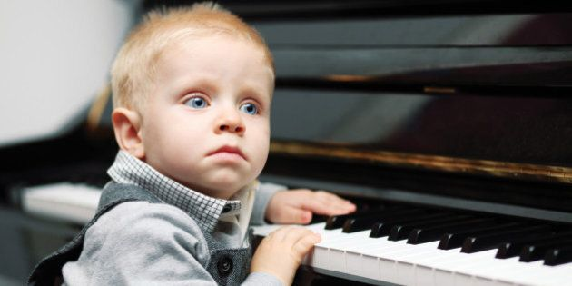 small genius sitting near piano - indoors