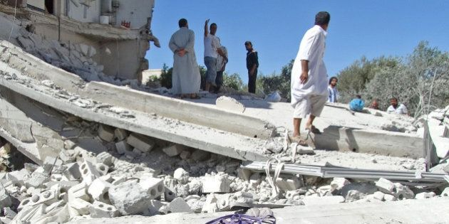 Men gather on the remains of a destroyed building after reported air strikes by Syrian government forces...