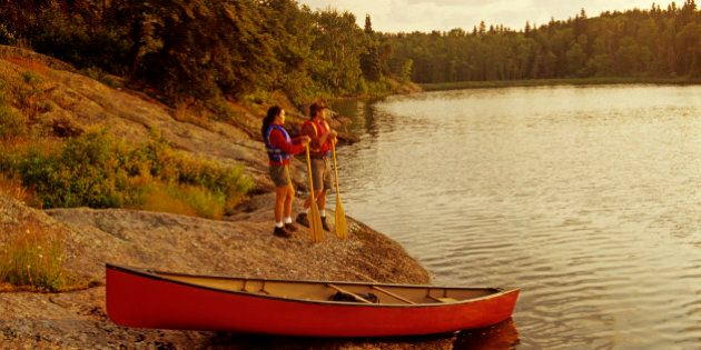 couple with canoe along Big Whiteshell Lake, Whiteshell Provincial Park, Manitoba,