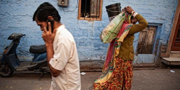 Man talking on mobile phone and woman carrying bags on her head in a typical blue street in old town....