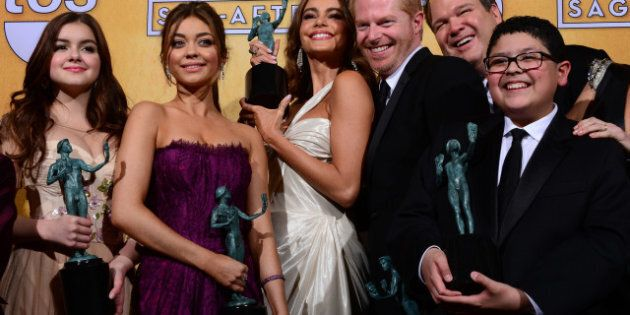 The cast of Modern Family poses with the Screen Actors Guild Award for for Oustanding Performance by...