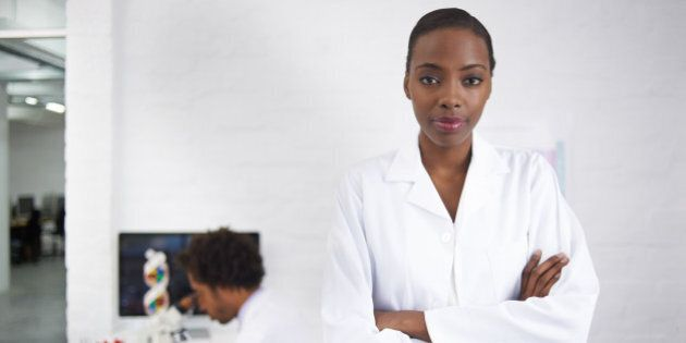 Portrait of a female biologist with her colleague working in the background