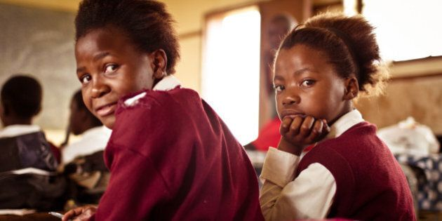 South African girl (from the Xhosa tribe) works on her studies at an old worn desk in a class room in...