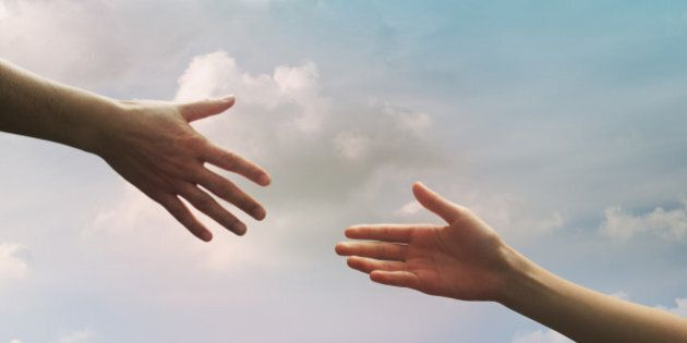 Hand of father and daughter seem to reach together in the sky