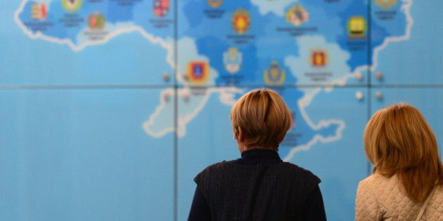 Women walk past a tourist map of the Ukraine at the Ukraine stand of the ITB International Travel Trade...