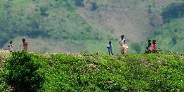 Haitian children stand on a ridge alongside the road known as La Internacional that divides Hispaniola...