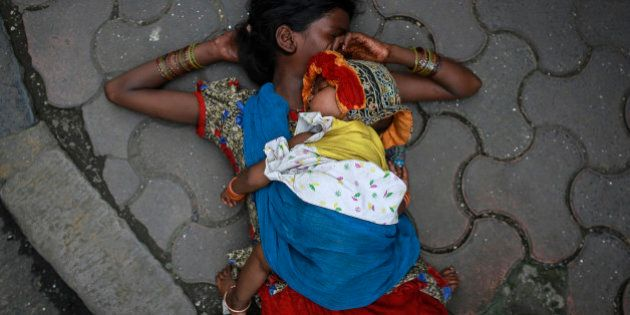 A woman sleeps with her baby on sidewalk at a market in Mumbai August 13, 2014. REUTERS/Danish Siddiqui (INDIA - Tags: SOCIETY)