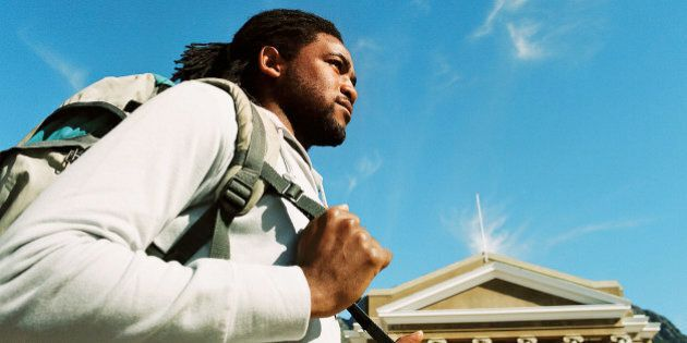 Low angle view of a young man carrying a shoulder bag