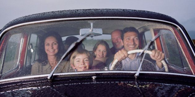 Family in vintage car, smiling,