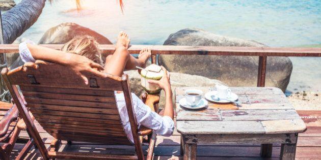Young woman enjoys drinking coffee and coconut. Koh Phangan island,