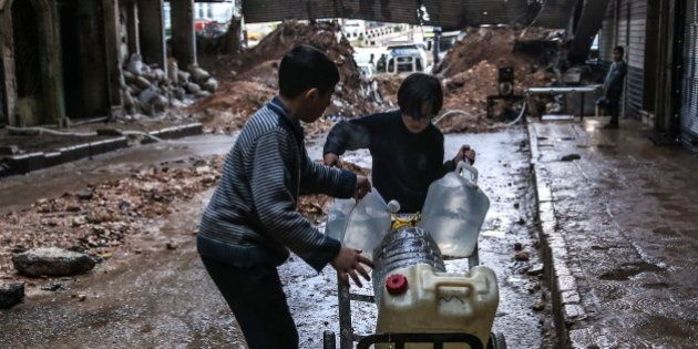 SYRIA. MARCH 5, 2016. Boys pull a trolley with containers of drinking water through a muddy street in Salah al-Din, Aleppo. Valery Sharifulin/TASS (Photo by Valery Sharifulin\TASS via Getty Images)
