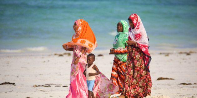 Kiwengwa Beach, Zanzibar, Tanzania - January 09, 2017: Local women with child walking along beach in...
