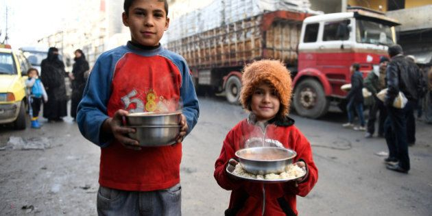 Children carry cooked meals provided by the UN through a partner NGO at al-Mashatiyeh neighborhood of east Aleppo, Syria, in this handout picture provided by UNHCR on January 4, 2017. Bassam Diab/UNHCR/Handout via Reuters  REUTERS ATTENTION EDITORS - THIS PICTURE WAS PROVIDED BY A THIRD PARTY. REUTERS IS UNABLE TO INDEPENDENTLY VERIFY THE AUTHENTICITY, CONTENT, LOCATION OR DATE OF THIS IMAGE. FOR EDITORIAL USE ONLY.