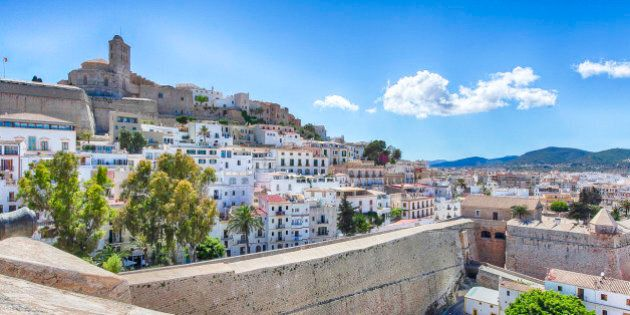 Sunny Panorama with a blue sky and few white clouds from the old town of Ibiza (old city of Eivissa) in Spain (Balearic Islands). Photo taken from the stone wall surrounding the city with a view of the Cathedral.