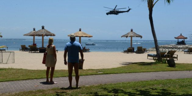 In this photograph taken on September 29, 2013, tourists watch Indonesian military helicopters patroling...