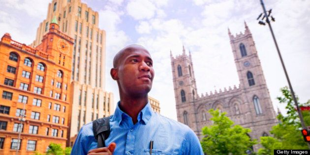 A young black businessman smiles with confidence as he goes to work in Old Montreal.