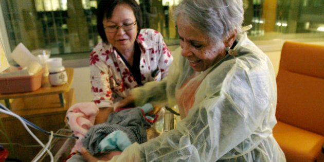 Hospital volunteer Gertie Rogers, 84, places a newborn baby back into a bed in the neonatal intensive...