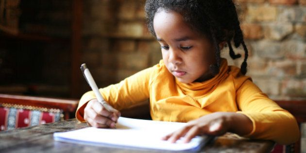 Profile of little African girl writing at