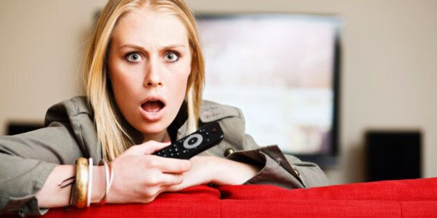 This cute young blonde woman holding a remote control seems utterly horrified by something she's seen...