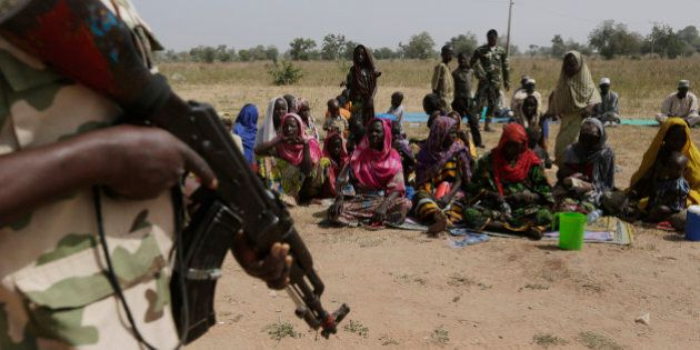 FILE- In this Tuesday, Dec. 8, 2015 file photo, soldiers guard people fleeing from Boko Haram's carnage...
