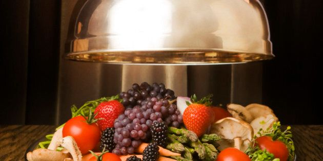 Silver lid lifted to show tray full of vegetable and fruit